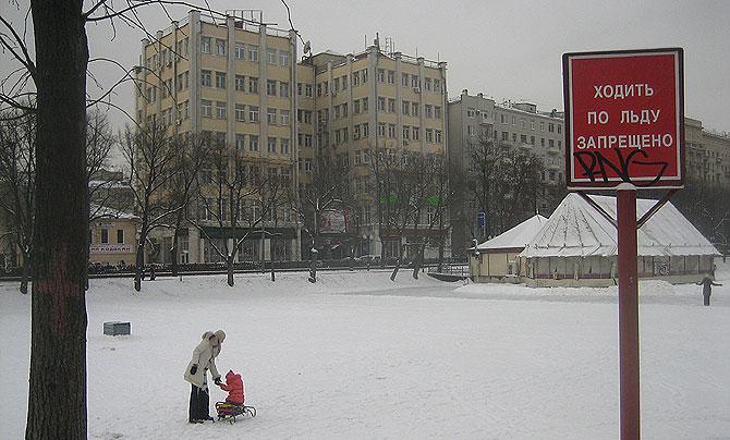 Una niña y una madre jugaban esta semana en el estanque helado de Chistiprudi, junto a un cartel donde se lee: 'Prohibido caminar sobre el hielo'. (Foto: Daniel Utrilla)