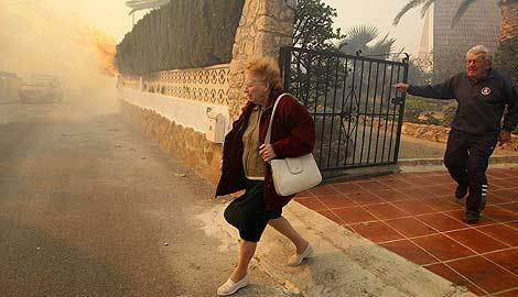 Dos personas huyen del fuego, próximo a su casa. | AFP