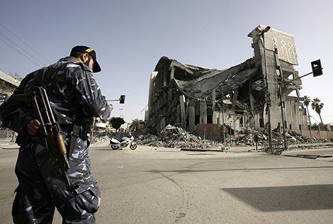 Un policia de Hamas patrulla cerca del Parlamento destruido por bombardeos israelíes. | Reuters