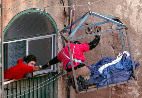 Un joven acerca una piruleta a otro, encerrado como protesta en una jaula. | EFE