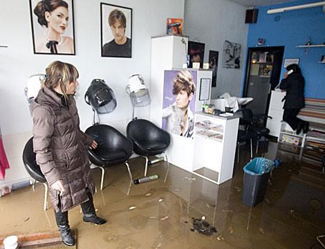 Una mujer observa cómo el agua ha anegado su peluquería en Irún.   Justy