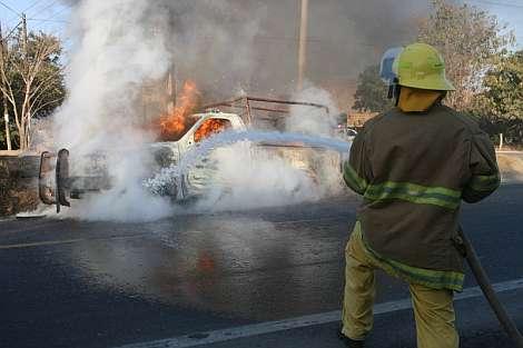 Un bombero apaga el fuego de la camioneta atacada. | EFE