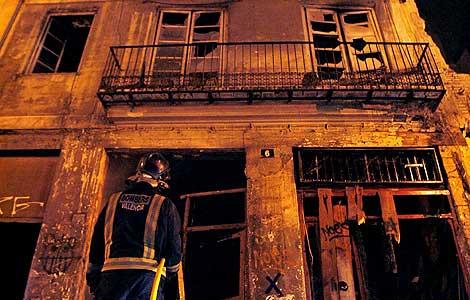 Un bombero observa la fachada del edificio donde se originó el incendio. (Foto: EFE)