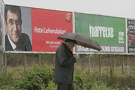 Un hombre pasa entre dos vallas publicitarias de Patxi López e Ibarretxe.   Mitxi