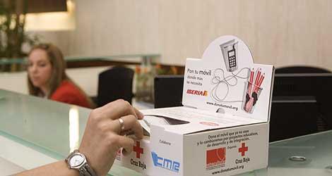 Una persona saca un sobre para donar su móvil en el aeropuerto.
