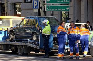Un policía municipal de Madrid multa a un coche que es retirado por la grúa. (Foto: Paco Toledo)