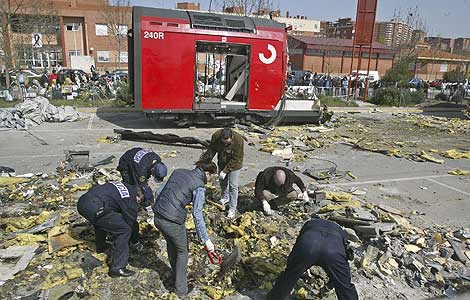 Varios policías rebuscan indicios relevantes para la investigación entre los restos del tren explosionado en la estación de El Pozo. | JULIÁN JAÉN