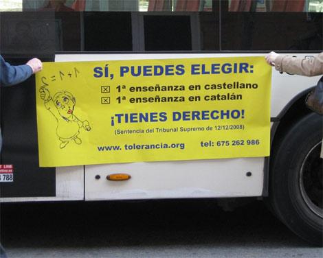 Aguantan un cartel de la campaña junto a un autobús de Barcelona.