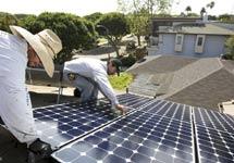 Dos trabajadores instalan un panel solar. | AFP