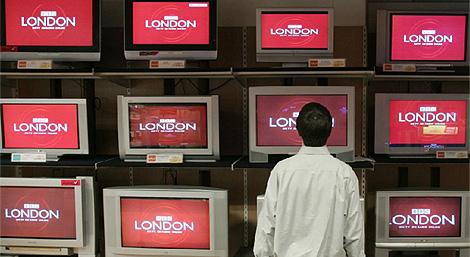 Un joven contempla varios televisores con la BBC en un escaparate.