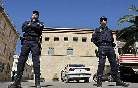 Dos policías custodian la entrada del Ayuntamiento de La Muela. | Efe