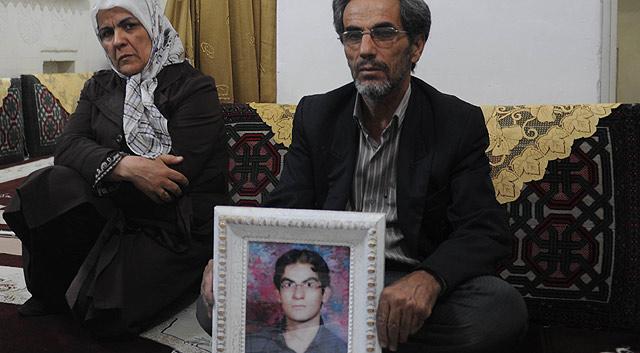 El taxista Aziz, junto a su esposa, sostiene la imagen de su hijo Majid. | Kaveh Kazemi