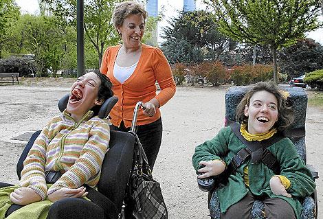 Ana García pasea por Madrid con sus dos hijas, María (dcha.) de 20 años y Clara, de 25, afectadas de parálisis cerebral. | Antonio Heredia