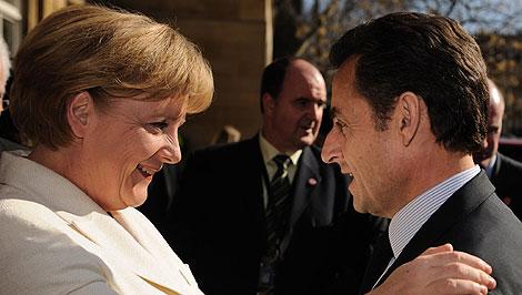 Merkel y Sarkozy se saludan antes de su reunión en Londres.   AFP