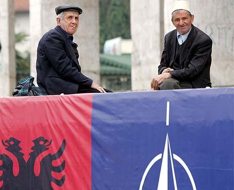 Dos albanos junto a un edificio con banderas de Albania y de la OTAN en Tirana. | Efe