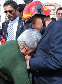 Berlusconi consuela a una mujer en L'Aquila. | AP