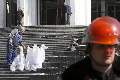 Un hombre recoge basura de los disturbios en la capital.   Efe