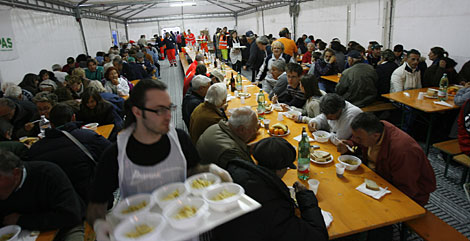 Damnificados comen en un campo de regugiados de L'Aquila. | AP