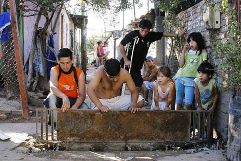 Unos adolescentes junto a las cloacas del barrio de Zavaleta, donde vive el mosquito que trasmite el dengue. (Foto: Alejandro Cherep)