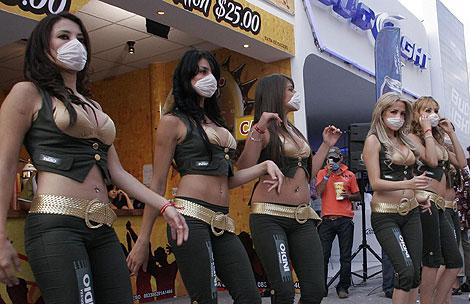 Un grupo de animadoras se cubren con mascarillas. | Efe
