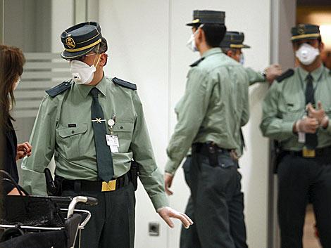 Guardias civiles con mascarillas, en el aeropuerto de Barajas. | Efe