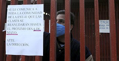 Un trabajador coloca un aviso sobre el cierre de los colegios. | Reuters