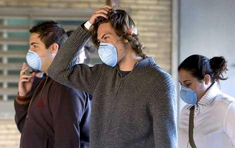 Tres jóvenes, con mascarillas, en el Hospital La Fe de Valencia.   Efe