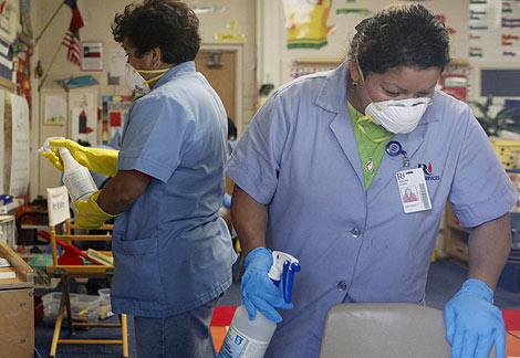 Varias limpiadoras, con máscaras en un colegio en Texas.   Reuters