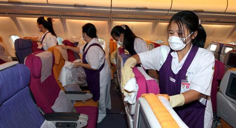 Varias operarias con mascarilla limpian la cabina de pasajeros de un avión de Thai Airways   Efe