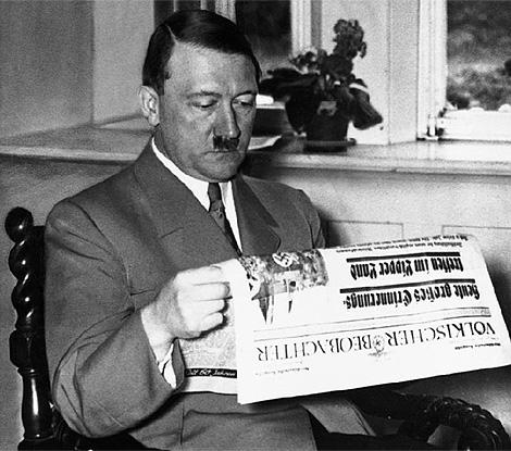 El alemán Adolf Hitler, enfrascado en la lectura de la prensa, en su despacho. (Foto: Corbis)