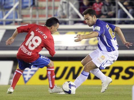 Quero intenta arrebatar el balón al centrocampista del Málaga Manuel Ortiz 'Lolo'.   Efe