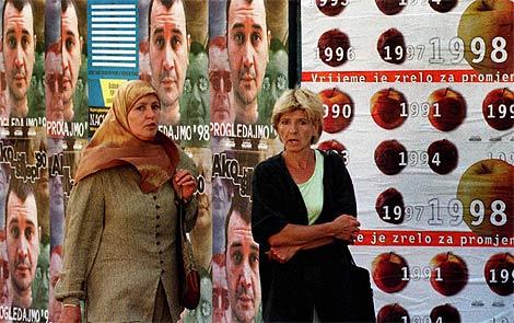 Dos mujeres pasean junto a carteles de las elecciones de 2008. | Ap