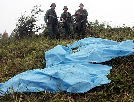 Varios militares, ante los cuerpos de sus compañeros. | Efe