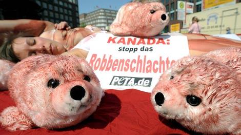 """Varios peluches de cría de foca y un cartel con la leyenda """"Canadá: ¡Acaba con el sacrificio de focas!"""", durante una protesta convocada por la organización en defensa de los animales PETA en Hamburgo (Alemania).   Efe"""