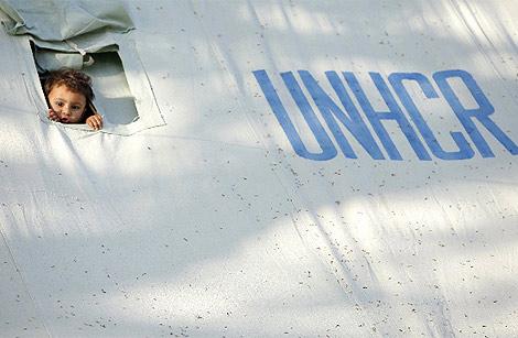 Un niño asoma la cabeza en una tienda de campaña de Naciones Unidas en un campo de refugiados al noroeste de Pakistán. (REUTERS)