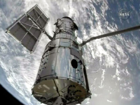 El telescopio 'Hubble' enganchado al brazo robótico del 'Atlantis'. / NASA TV