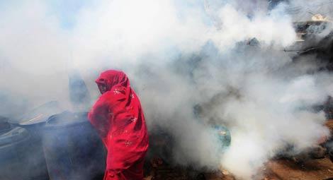 Una mujer se cubre la cara durante una fumigación contra el mosquito de la malaria en Bombay (La India). | Reuters