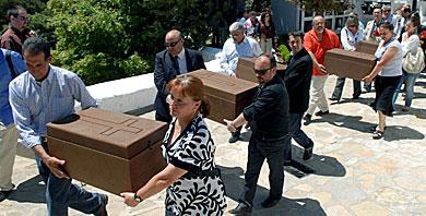 Los familiares trasladan los féretros con los restos de sus parientes. | Efe