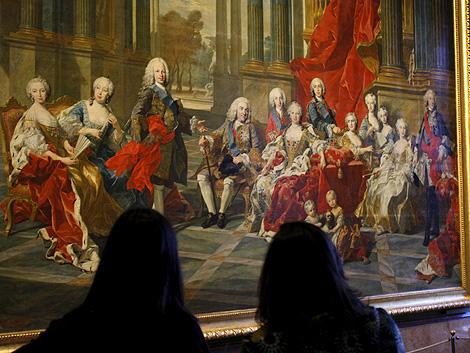 Dos visitantes del Prado, ante el cuadro 'La Familia de Felipe V', de Louis Michel van Loo, que se expone estos días en la capital. | Efe