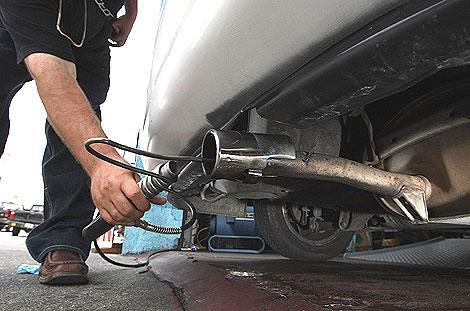 Un mecánico mide las emisiones de un automóvil. | Reuters