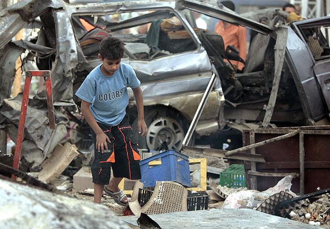 Un niño iraquí camina entre los restos de coches y cajas en un basurero iraquí. (Foto: AFP)