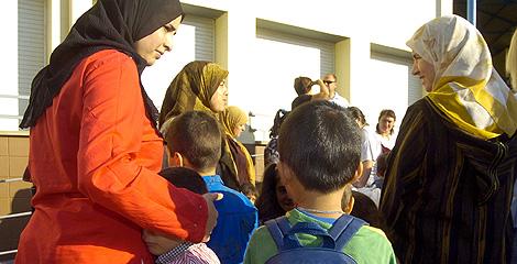 Una mujeres musulmanas llevana sus hijos al colegio.   Efe