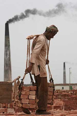 Un trabajador de una fábrica de ladrillos y al fondo una chimenea humeante en Bangladesh. | Ap
