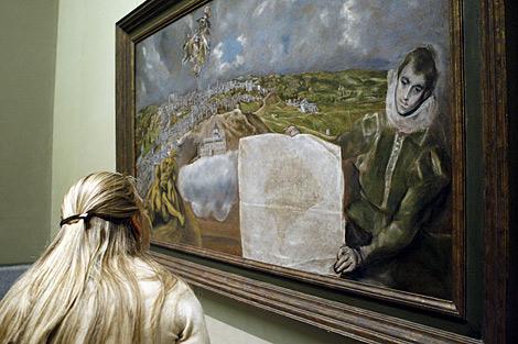 Una mujer observa el cuadro 'Vista y plano de Toledo' pintado por El Greco. | Efe.