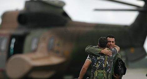 Dos miembros de las operaciones de búsqueda del avión de Air France se saludan. | AP