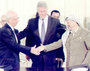 Isaac Rabin y Yaser Arafat se dan la mano bajo la mirada de Bill Clinton. (Foto: Reuters)