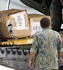 Un operario carga un avión militar con bolsas para cadáveres en la isla de Fernando de Noronha. | Efe