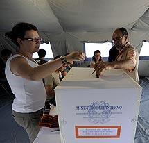Un hombre vota en una tienda de campaña en L'Aquila. | AFP