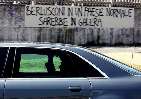 El primer ministro italiano pasa frente a un graffiti dirigido contra él. 'Berlusconi en un país normal estaría en prisión' se lee. | David Bebber