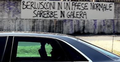 El primer ministro ante el cartel: 'Berlusconi en un país normal estaría en prisión'.